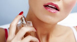 Photo of sensual woman spraying perfume onto her neck skin